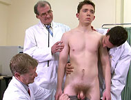 Three clothed doctors examine and fondle sporty young bloke who plays rugby muscular naked body